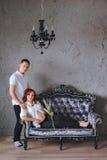 Donna incinta sul sofà grigio Stando accanto al suo marito Immagini Stock