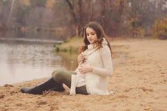 Donna incinta sulla passeggiata all'aperto di autunno, umore caldo accogliente Fotografia Stock
