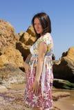 Donna incinta sulla spiaggia vicino alle rocce immagine stock libera da diritti