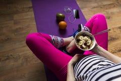 Donna incinta sulla stuoia che mangia la farina d'avena sana della prima colazione con Fotografia Stock Libera da Diritti