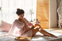 Donna incinta sveglia che si siede sul letto e che beve il suo caffè di mattina fotografia stock