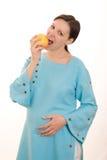 Donna incinta in un vestito blu che mangia una mela Fotografia Stock Libera da Diritti