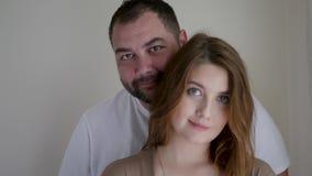 Donna incinta in un vestito marrone e nel suo marito in una maglietta bianca stock footage