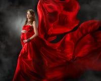 Donna incinta in vestito rosso da volo fotografia stock