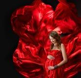 Donna incinta in vestito rosso da volo immagine stock libera da diritti
