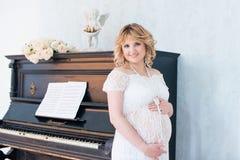 Donna incinta vicino al piano Fotografia Stock