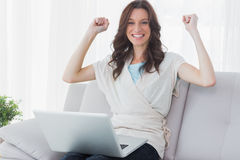 Donna incoraggiante con il computer portatile sulle sue ginocchia Immagine Stock