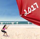 Donna indiana che tira i numeri 2017 sulla spiaggia Immagini Stock