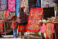 Donna indiana peruviana che esamina i tessuti variopinti Fotografia Stock