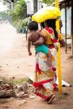 Donna indiana in sari variopinti con la balla di trasporto del bambino sulla testa Fotografie Stock