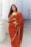 Donna indiana in Sari Walking con i fiori Fotografie Stock