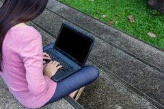 Donna indipendente che per mezzo del computer portatile Immagini Stock
