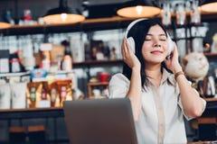Donna indipendente di stile di vita lui facendo uso del dur d'ascolto di musica delle cuffie Immagine Stock Libera da Diritti