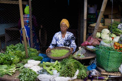 Donna indonesiana che vende gli ortaggi freschi al mercato a Samarang Fotografie Stock