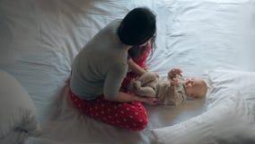 Donna in indumenti da notte con il bambino adorabile sul letto Mamma di amore che gioca con il neonato video d archivio