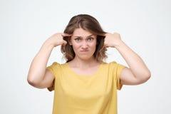 Donna infastidita arrabbiata del ritratto che si infuria indicando dito alla sua testa fotografie stock