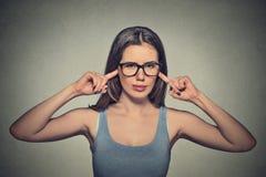 Donna infelice arrabbiata con i vetri che tappano le orecchie con le dita Fotografia Stock Libera da Diritti