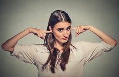 Donna infelice arrabbiata con le orecchie chiuse che vi esaminano Immagini Stock