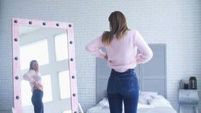 Donna infelice che controlla grasso sul suo corpo a casa video d archivio