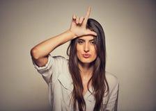 Donna infelice che dà il segno del perdente sulla fronte, esaminante vi, repulsione sul fronte Fotografie Stock Libere da Diritti