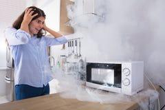Donna infelice che esamina fumo che emette attraverso il forno a microonde immagine stock