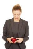 Donna infelice che esamina il suo portafoglio Fotografia Stock