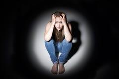 Donna infelice che si siede nello stagno di luce Immagini Stock Libere da Diritti