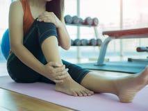 Donna infelice che si siede sulla stuoia di yoga con la ferita alla caviglia fotografia stock libera da diritti