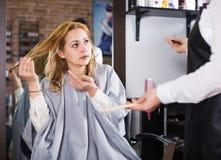 Donna infelice nel salone dei hairdress Fotografie Stock Libere da Diritti
