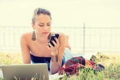 Donna infelice scettica triste che manda un sms sul telefono all'aperto nel parco Immagine Stock