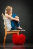 Donna infelice triste con il cuscino rosso del cuore Fotografie Stock