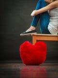 Donna infelice triste con il cuscino rosso del cuore Immagini Stock Libere da Diritti