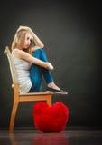 Donna infelice triste con il cuscino rosso del cuore Fotografia Stock Libera da Diritti
