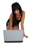 Donna inginocchiata che lavora al computer portatile Immagini Stock