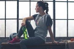 Donna in ingranaggio di allenamento che si siede sul banco nel sottotetto della città che guarda fuori Immagini Stock