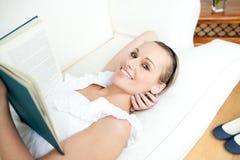 Donna intelligente che legge un libro che si trova su un sofà Immagini Stock Libere da Diritti