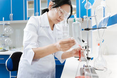 Donna intelligente seria che lavora con i reagenti chimici Fotografia Stock