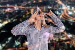 Donna intrigante in cuffia avricolare d'uso di realtà virtuale 3D della camicia grigia fotografia stock libera da diritti