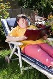 Donna invalida che legge un libro nel giardino Fotografia Stock