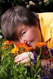 Donna invalida che si trova sull'erba e sull'odore dei fiori Fotografia Stock Libera da Diritti
