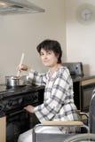 Donna invalida in sedia a rotelle che cucina pranzo Immagini Stock
