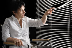 Donna invalida in sedia a rotelle che osserva i ciechi della depressione immagine stock