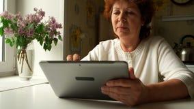 Donna invecchiata che per mezzo di un PC digitale della compressa a casa Immagine Stock