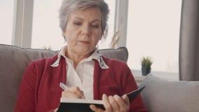 Donna invecchiata che si siede a casa e che scrive in taccuino video d archivio