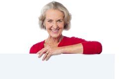 Donna invecchiata che sta dietro il tabellone per le affissioni in bianco Fotografia Stock