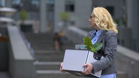 Donna invecchiata con il contenitore di roba che lascia l'edificio per uffici, età di pensionamento, opportunità del lavoro video d archivio