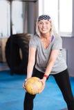 Donna invecchiata contentissima che si esercita con una palla Fotografie Stock Libere da Diritti