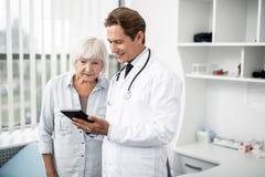 Donna invecchiata curiosa che esamina lo schermo di sorridere di medico e della compressa immagine stock