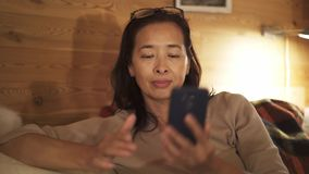 Donna invecchiata media asiatica che compone un numero e che parla a casa stock footage