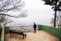 Donna invecchiata media con la vista panoramica della città dalla collina di Mtatsminda, Tbilisi, Georgia immagine stock